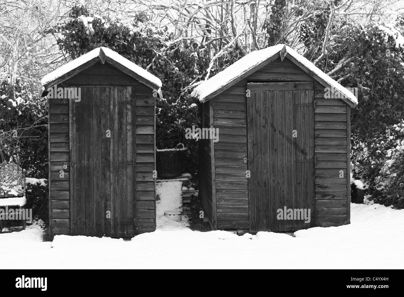 Wooden sheds in a snow-covered garden - Stock Image