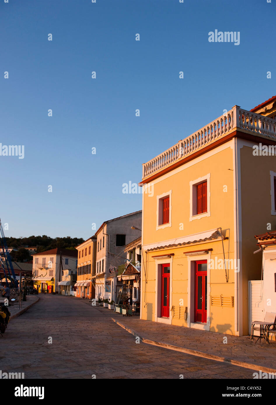 The sun rises over the waterfront stores of Gaios harbour. Paxos, Greece. - Stock Image