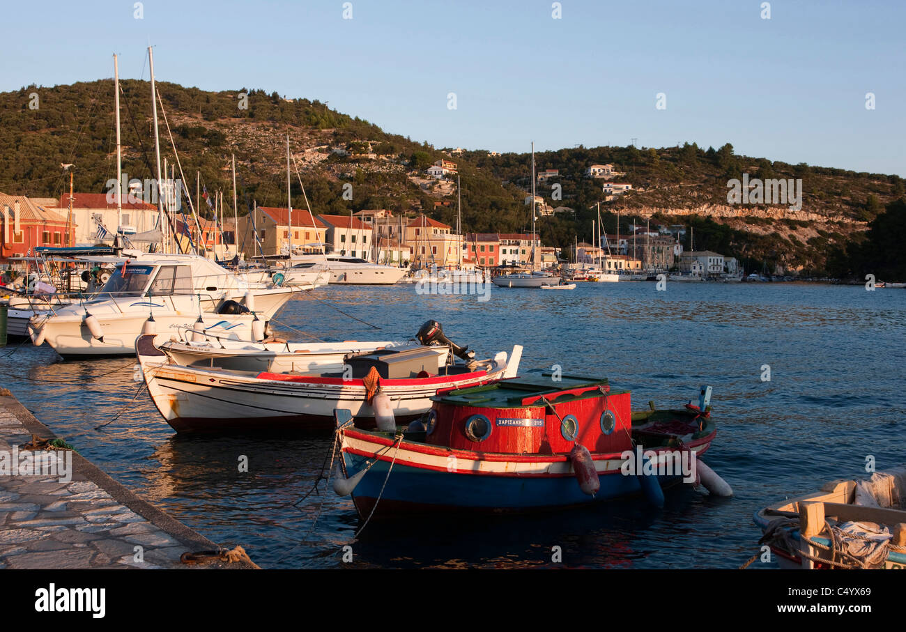 The sun rises over the waterfront in Gaios harbour. Paxos, Greece. - Stock Image