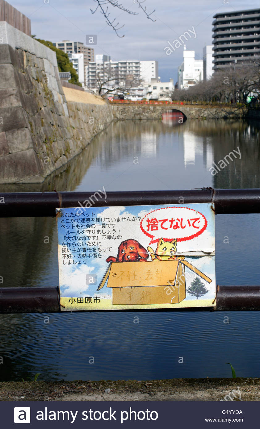 An appeal by the city council to people not to abandon unwanted pets, beside the moat of Odawara Castle and park. - Stock Image