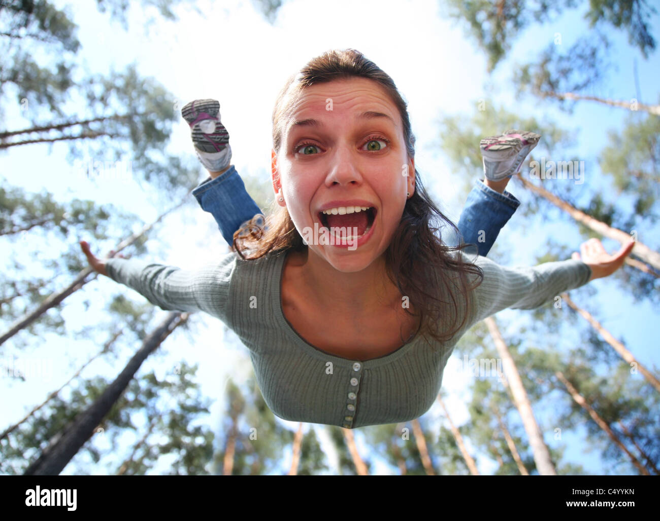 Woman falls from above the pine forest directly at you. - Stock Image