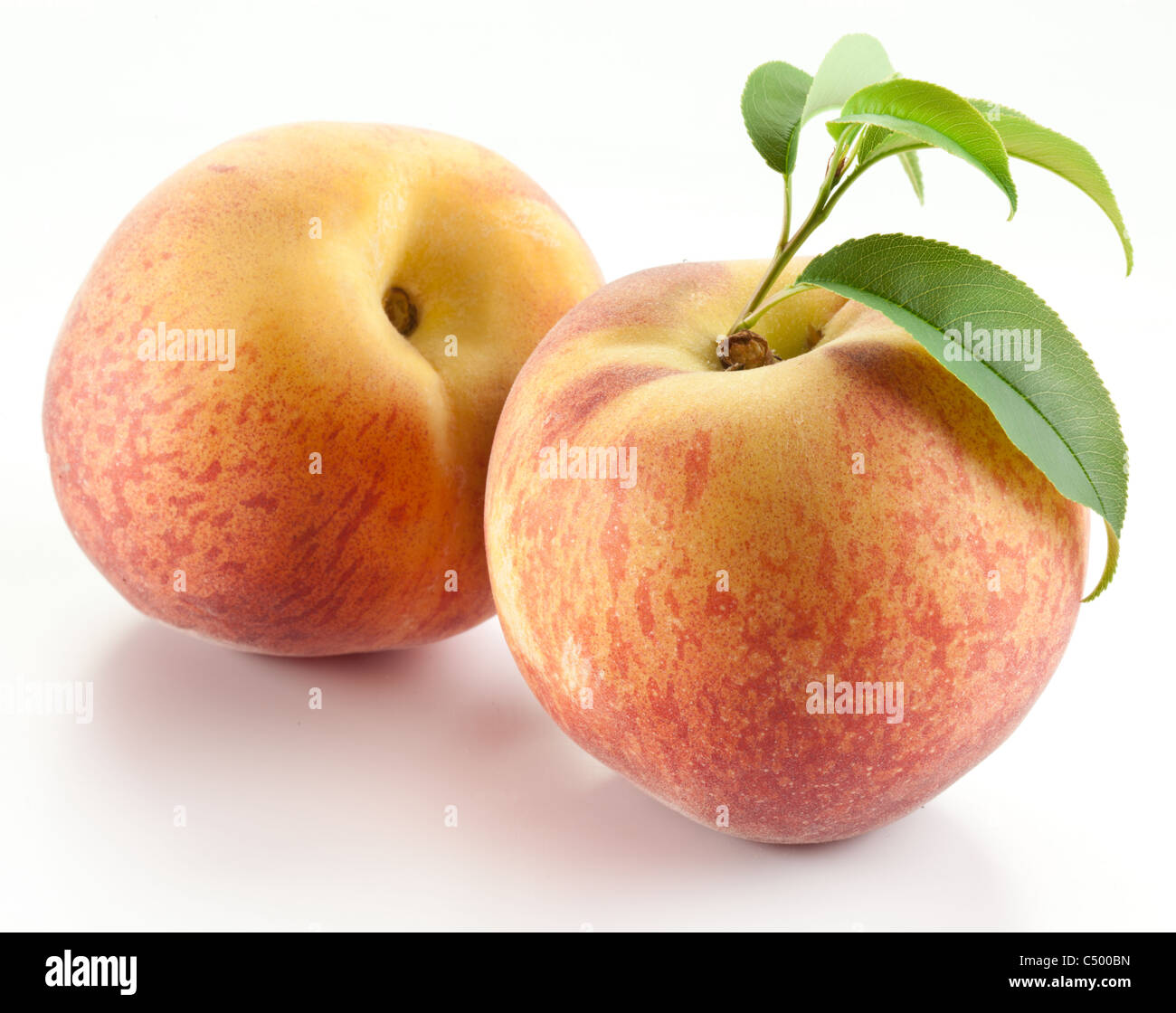 Two ripe peach with leaves on white background. - Stock Image