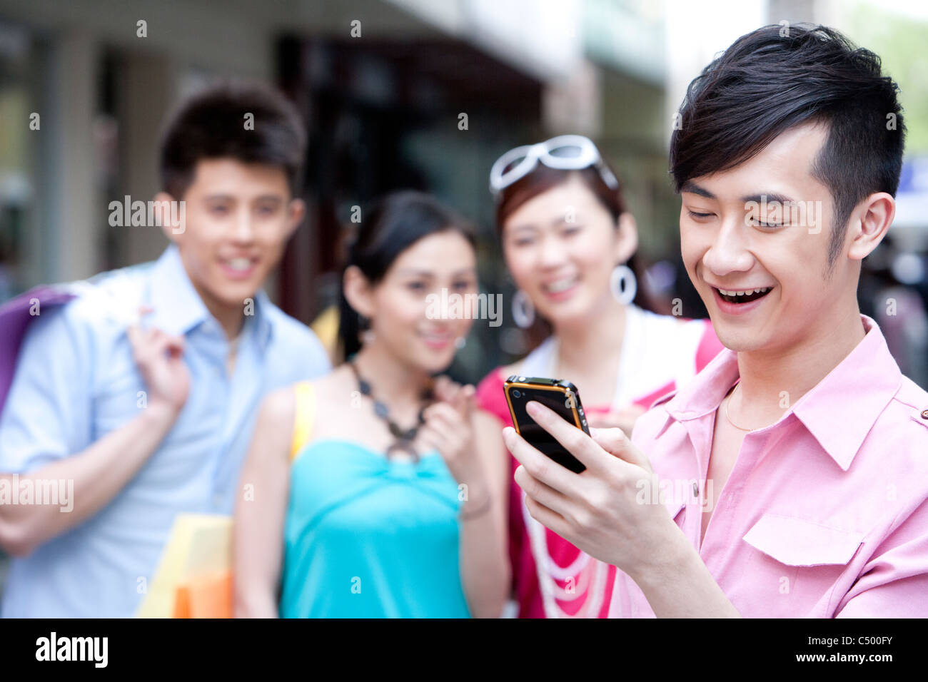 Young Man Using Phone In Front of Friends - Stock Image