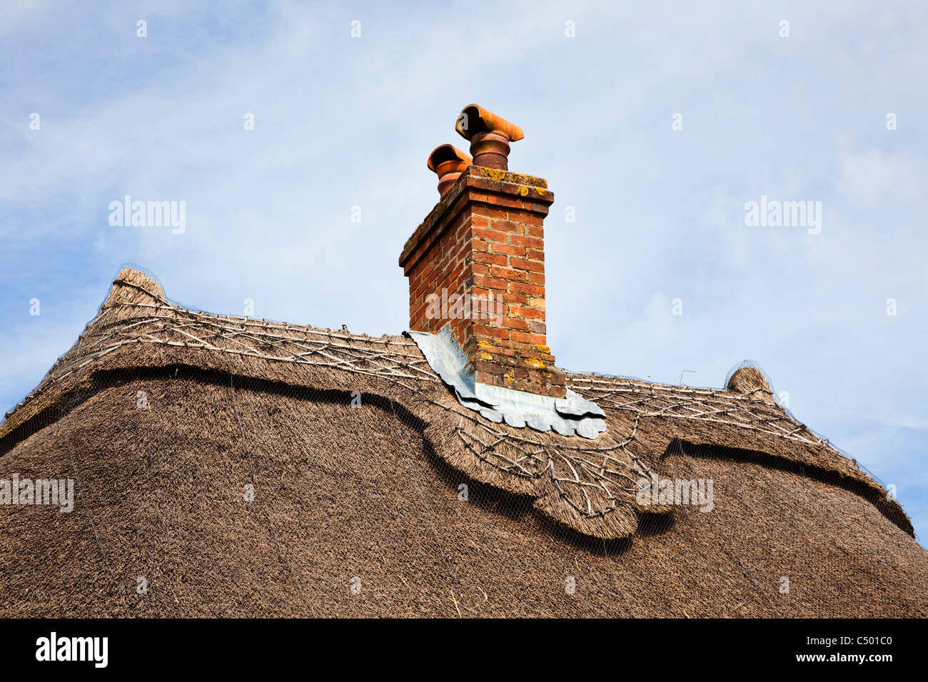Thatched roof detail and chimney on a small old house England UK - Stock Image