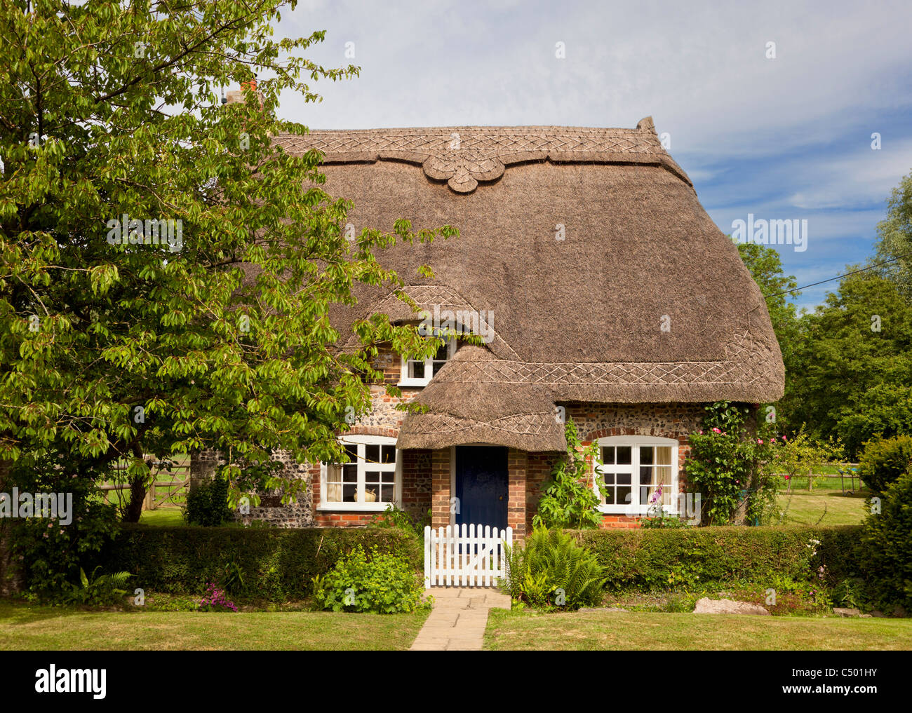 Tiny old thatched cottage in the pretty village of Tarrant Monkton, Dorset, England, UK - Stock Image