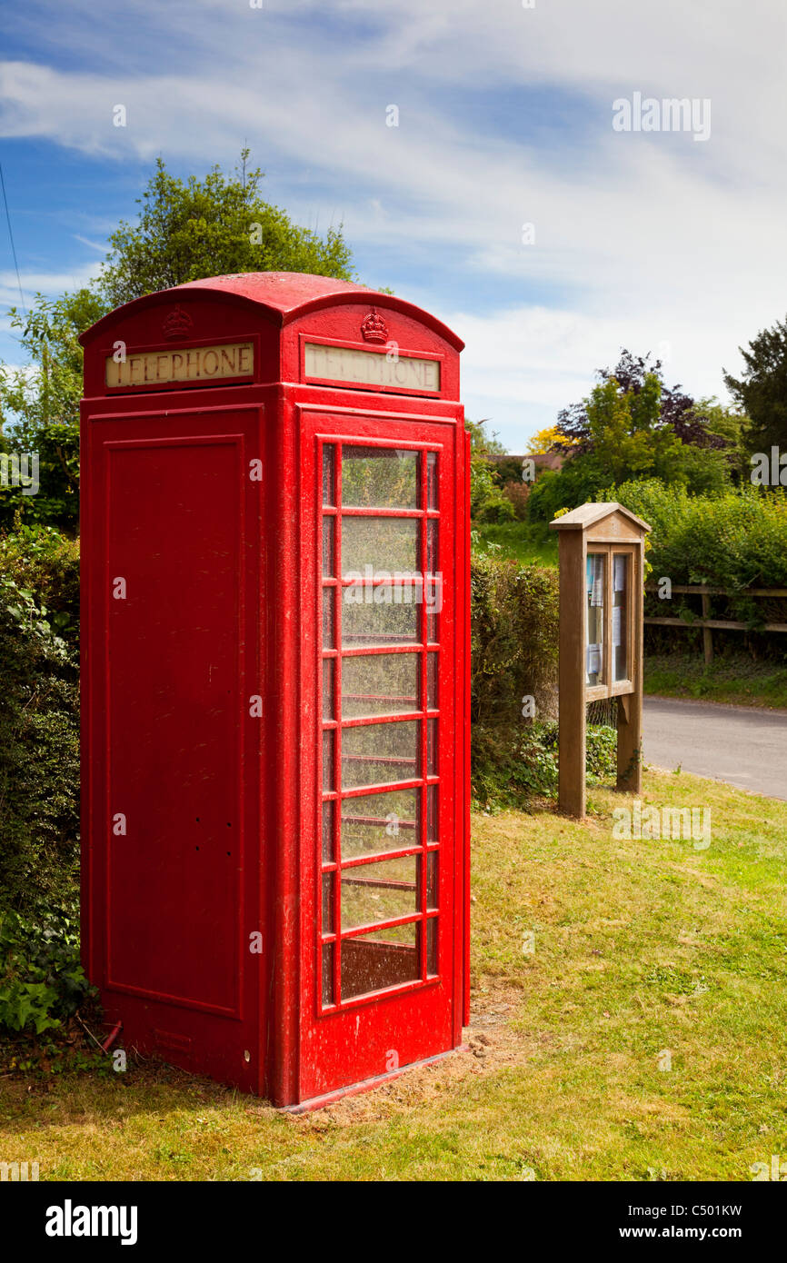 Traditional British red phone box and village noticeboard, England, UK - Stock Image