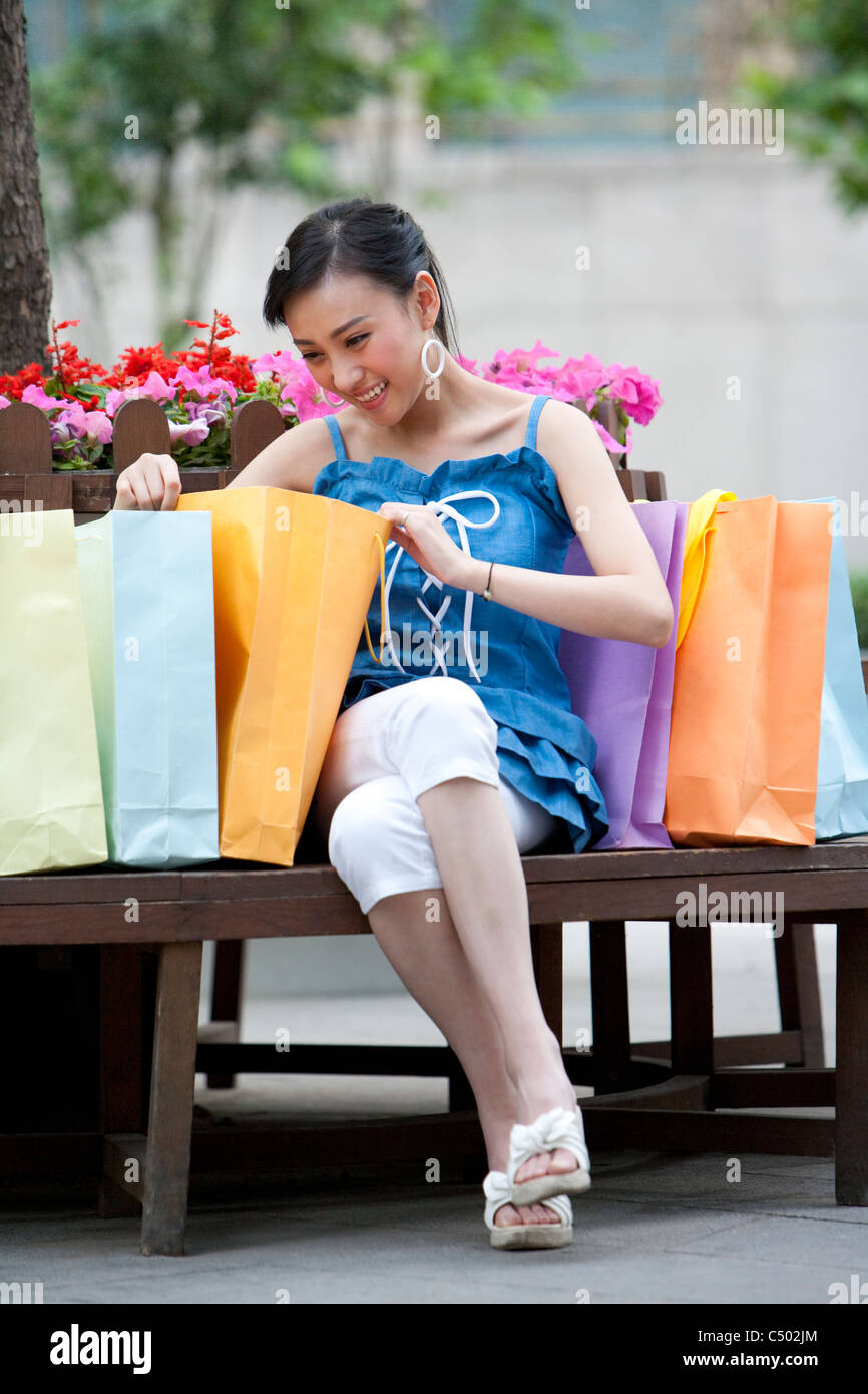 Young Woman Looking Through Shopping Bags - Stock Image