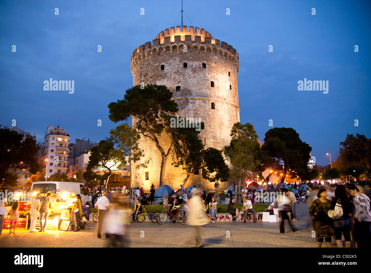 a busy evening at the illuminated white tower, symbol of the town of Thessaloniki, Macedonia, Greece - Stock Image