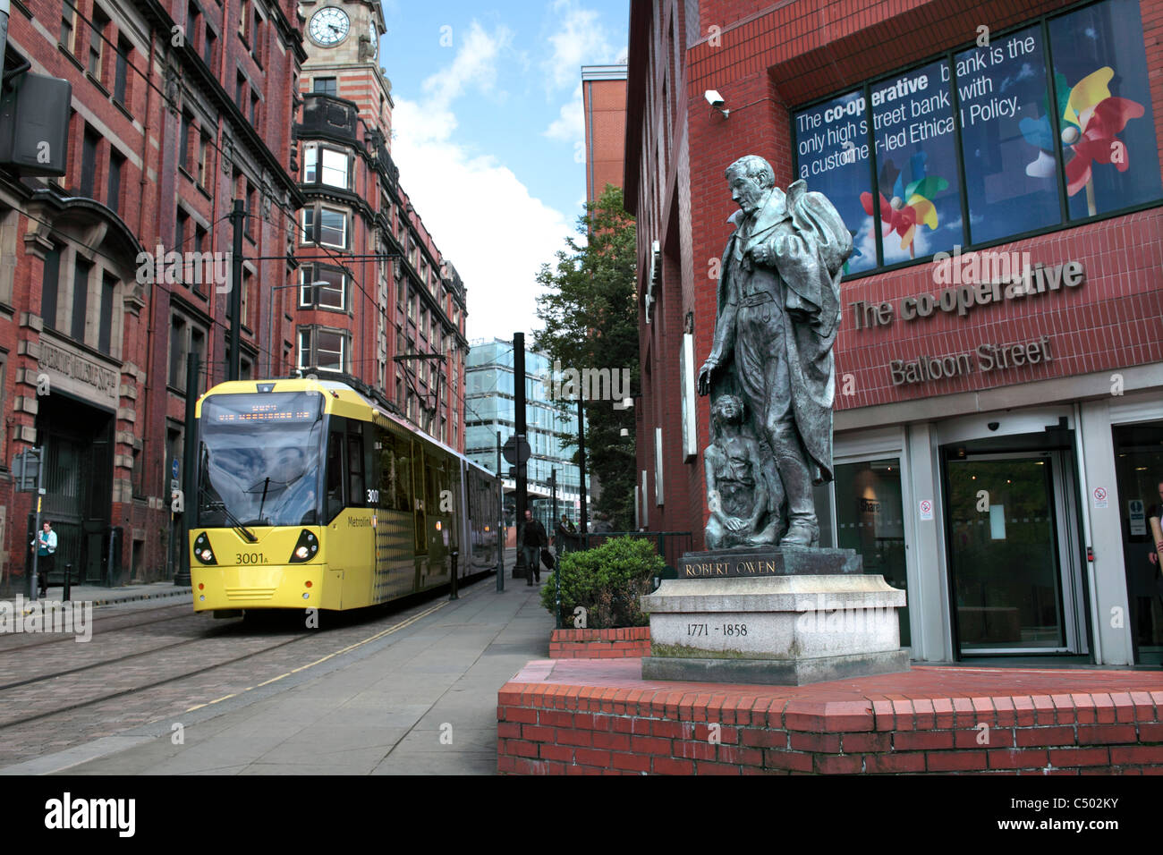 A tram passing a statue of Robert Owen outside the Co-op Bank on Balloon Street, Manchester. - Stock Image