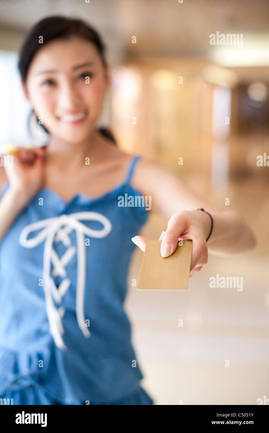 Young Woman Holding Out a Credit Card - Stock Image
