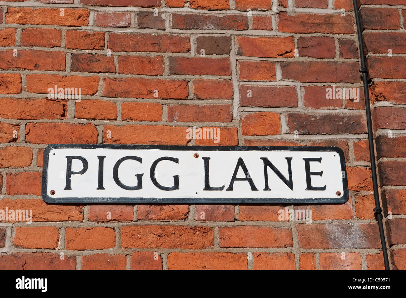 Traditional street name plate fixed to a brick wall on Pigg Lane in Norfolk, England. - Stock Image