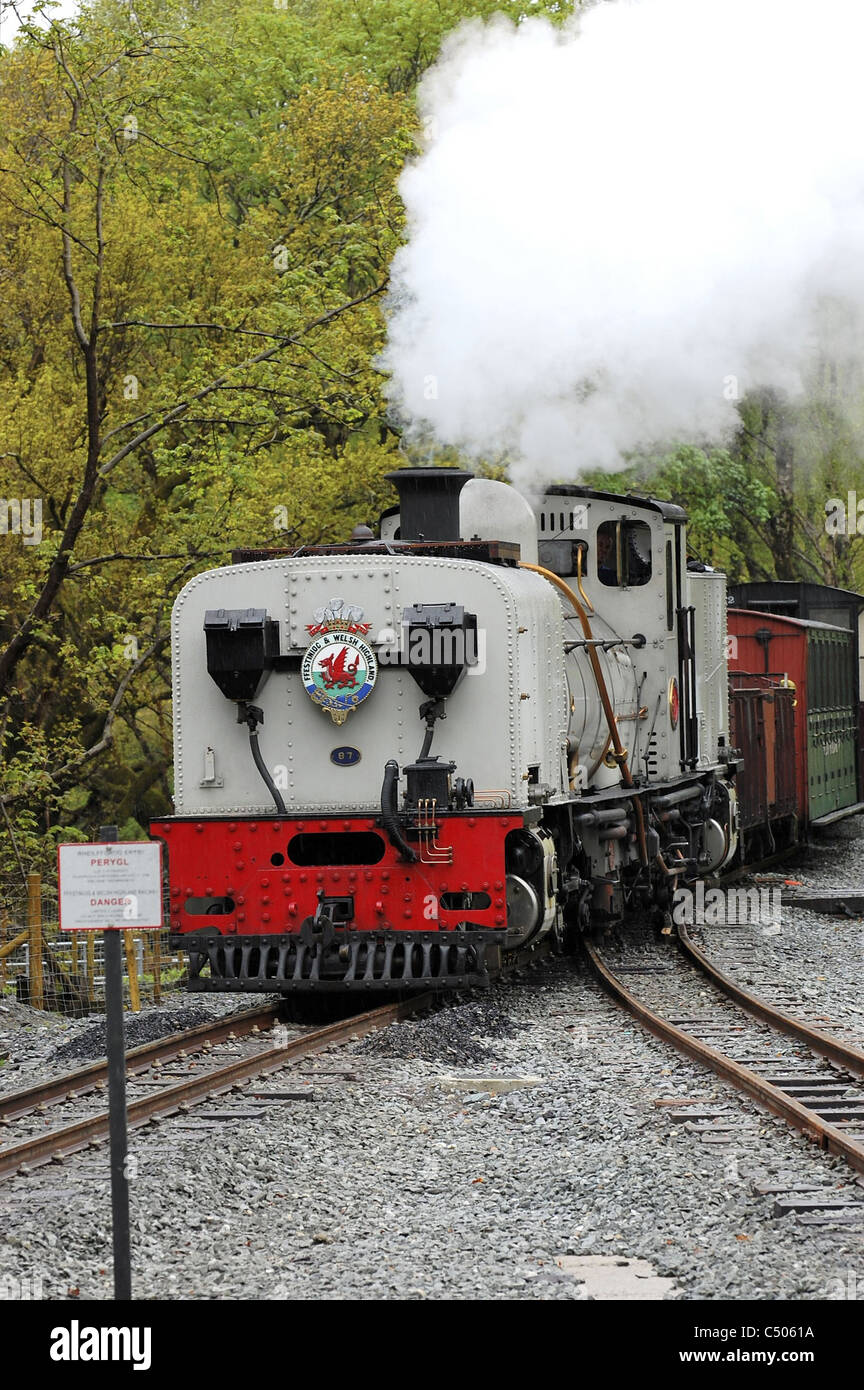 White steam locomotive approaching station - Stock Image