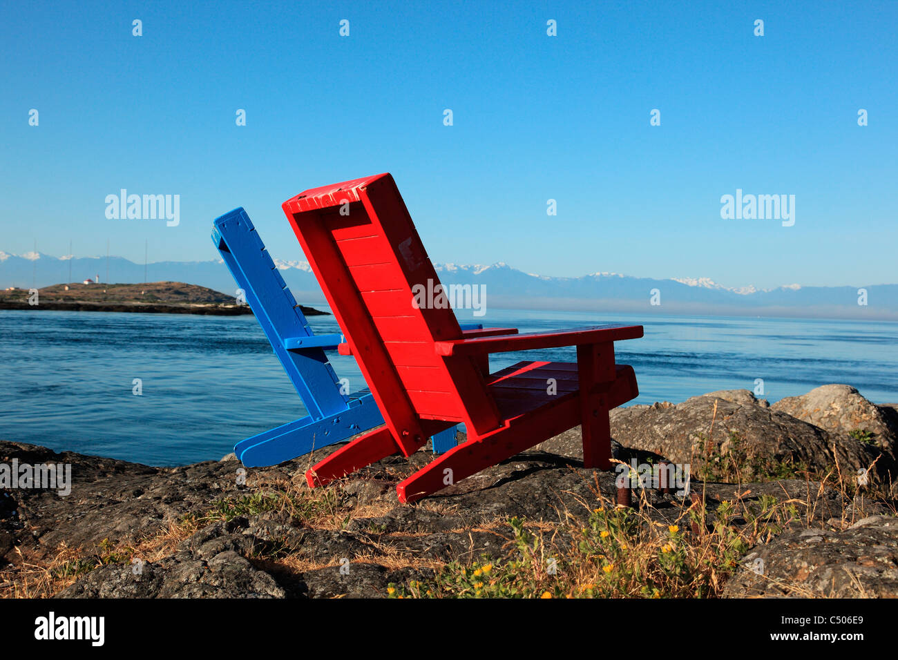 Red and Blue chairs sitting on rocks looking out to the pacific ocean on a calm sunny summer morning in Victoria - Stock Image