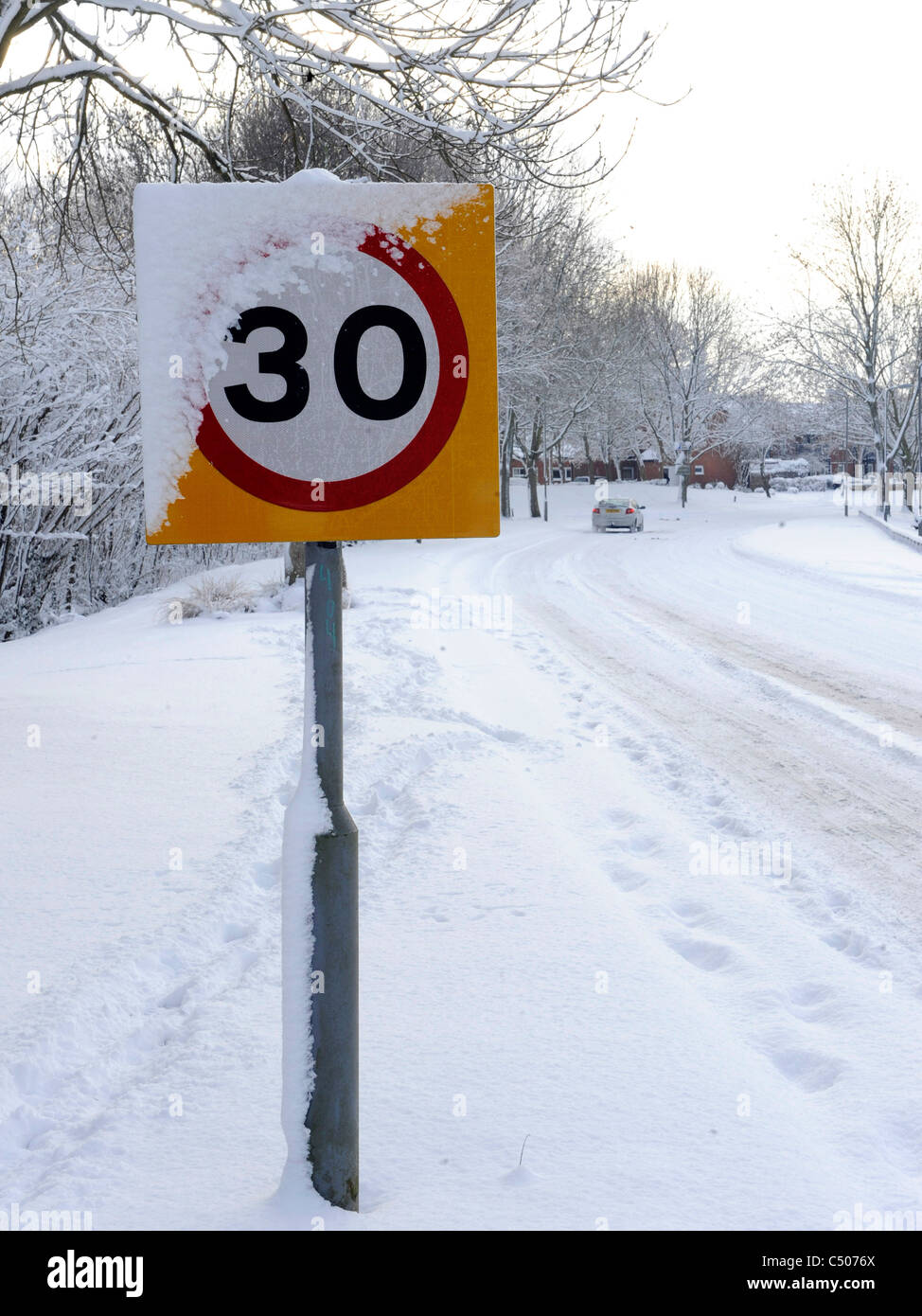 A snow covered speed limit sign. - Stock Image