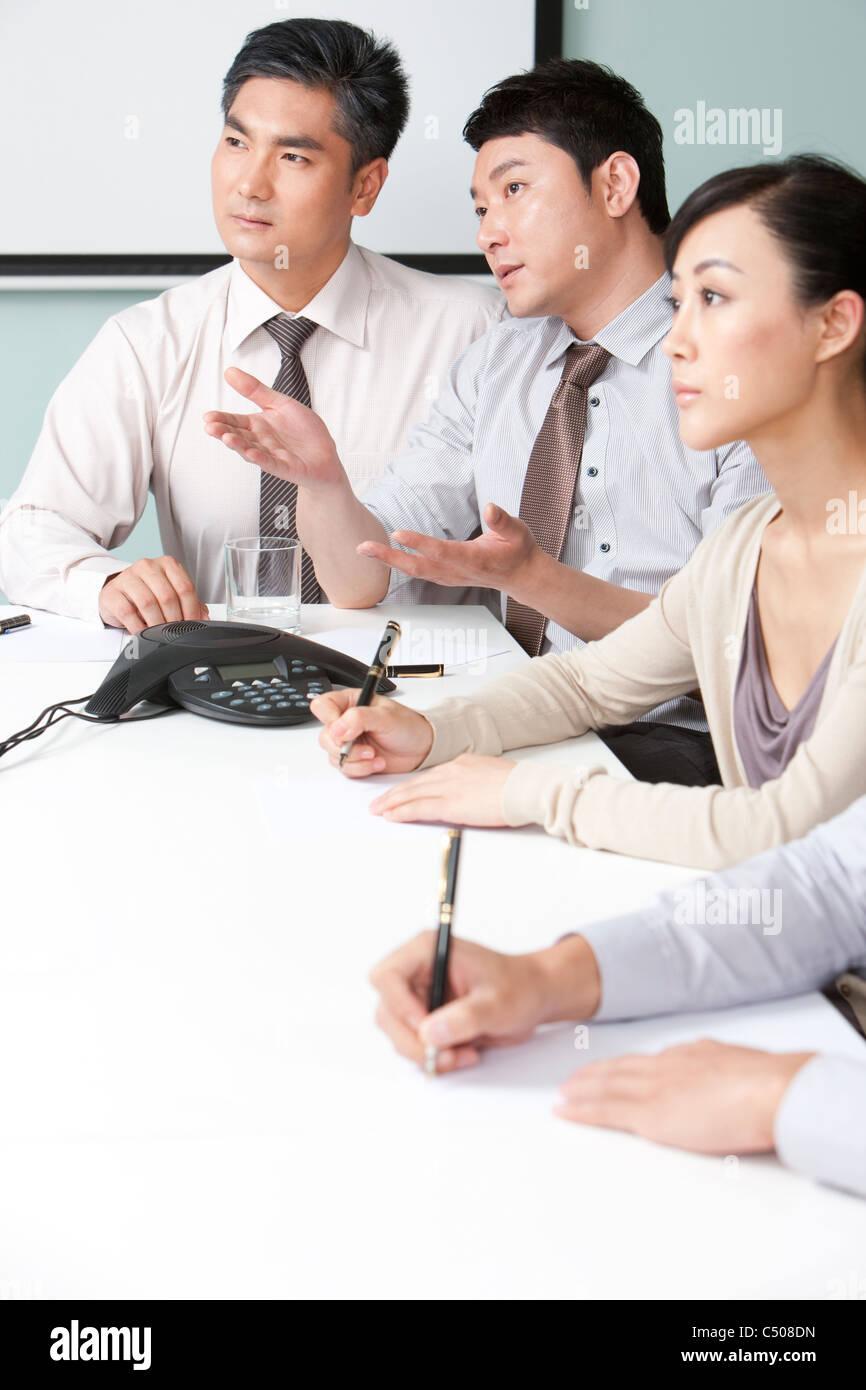 Businessmen Deliberating in Meeting - Stock Image