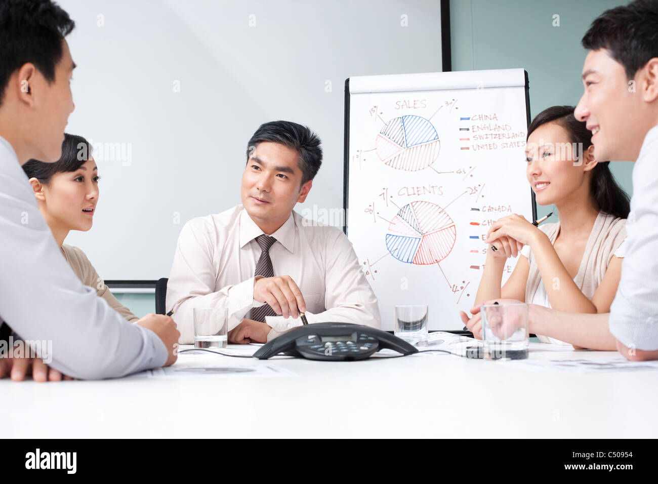 Business Executive Listening to Businessman's Question - Stock Image