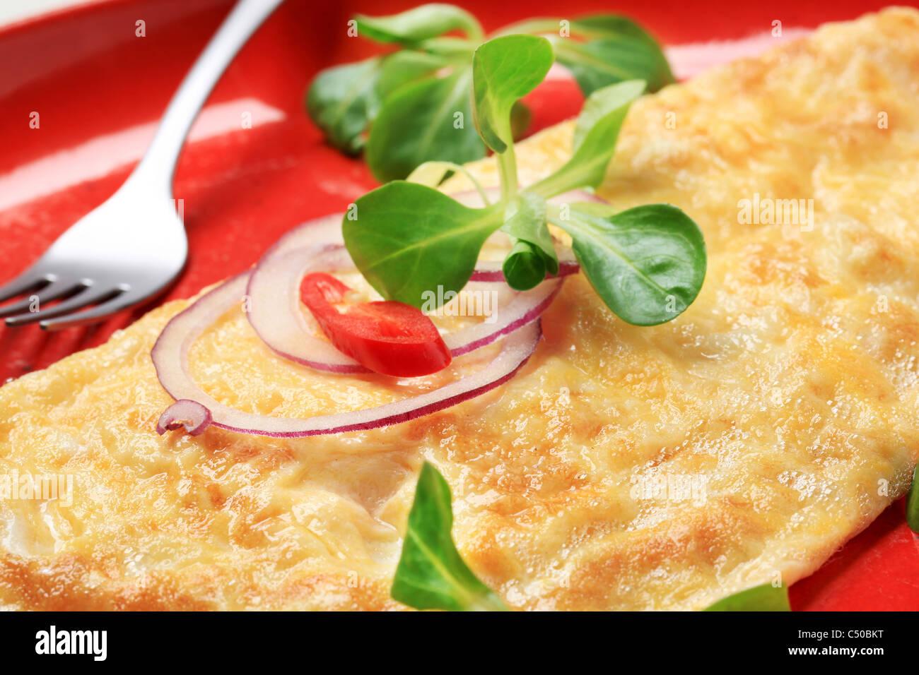 Egg omelet sprinkled with fresh salad greens - Stock Image