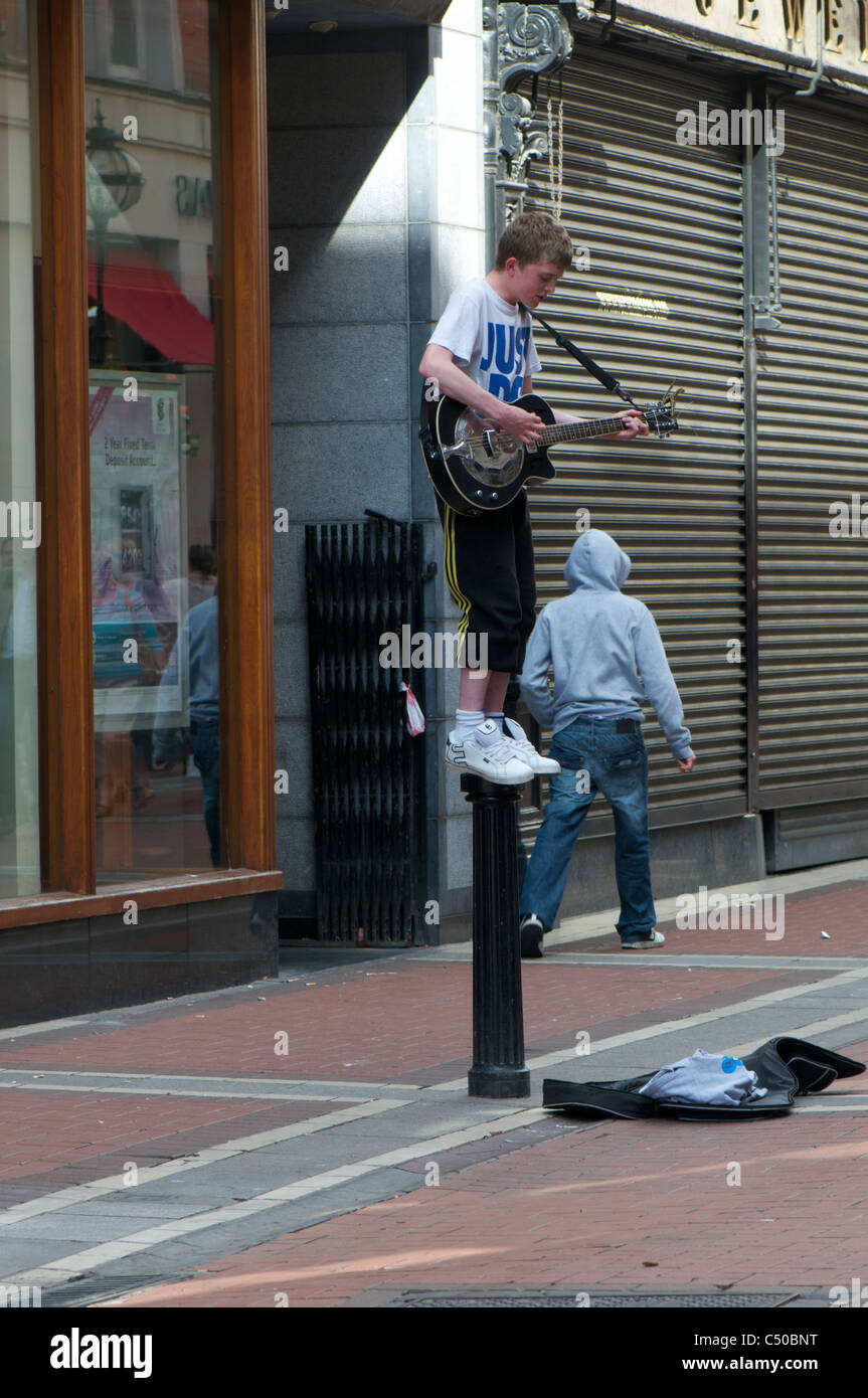 Busker on a poll - Stock Image