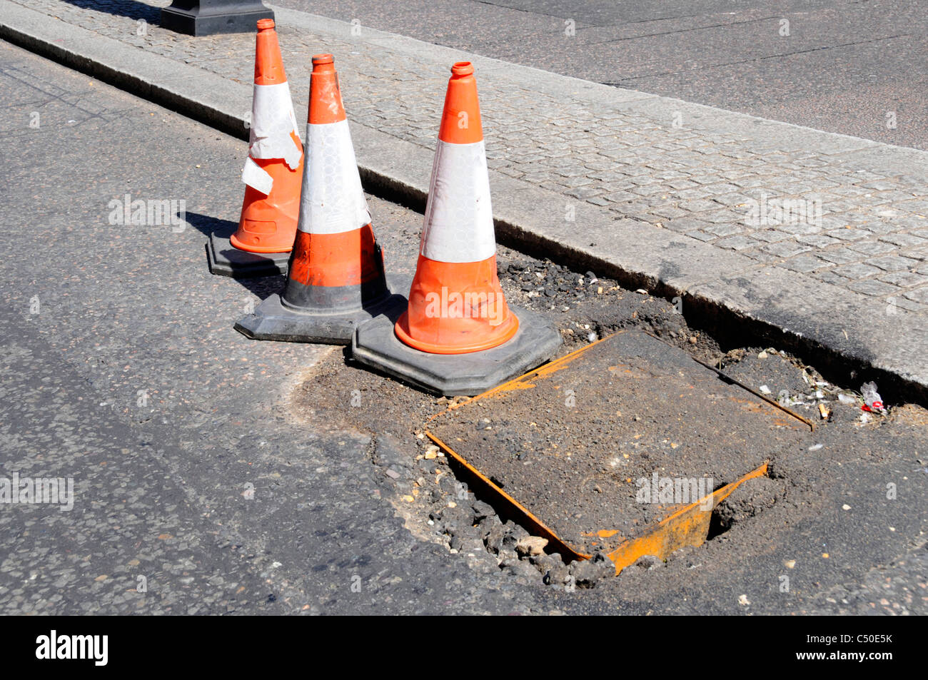 Potholes around manhole cover in London street - Stock Image