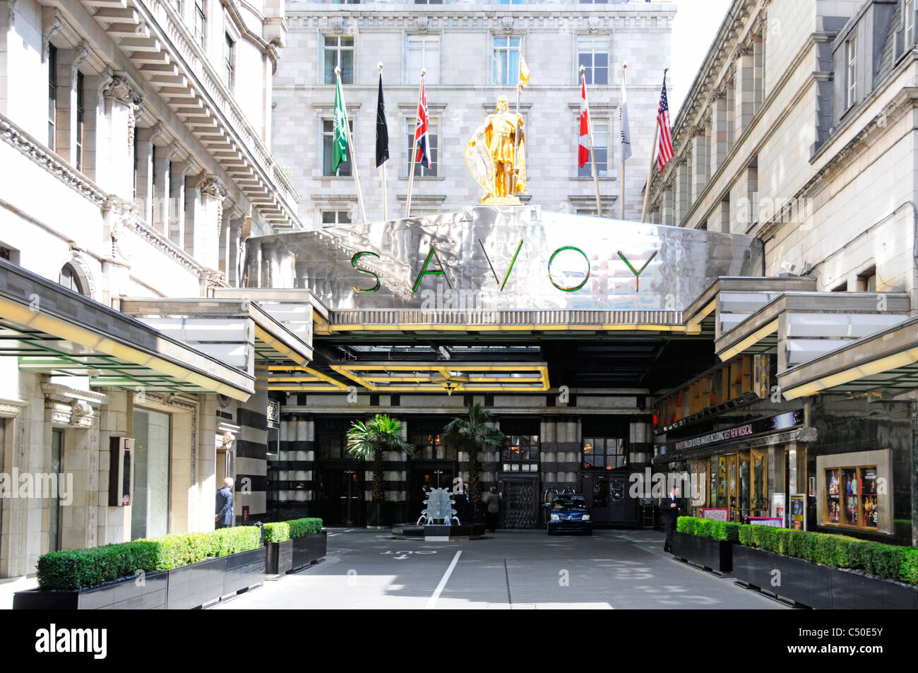 Savoy Hotel sign flags & statue above Savoy Court entrance to this London street West End luxury hotel England - Stock Image
