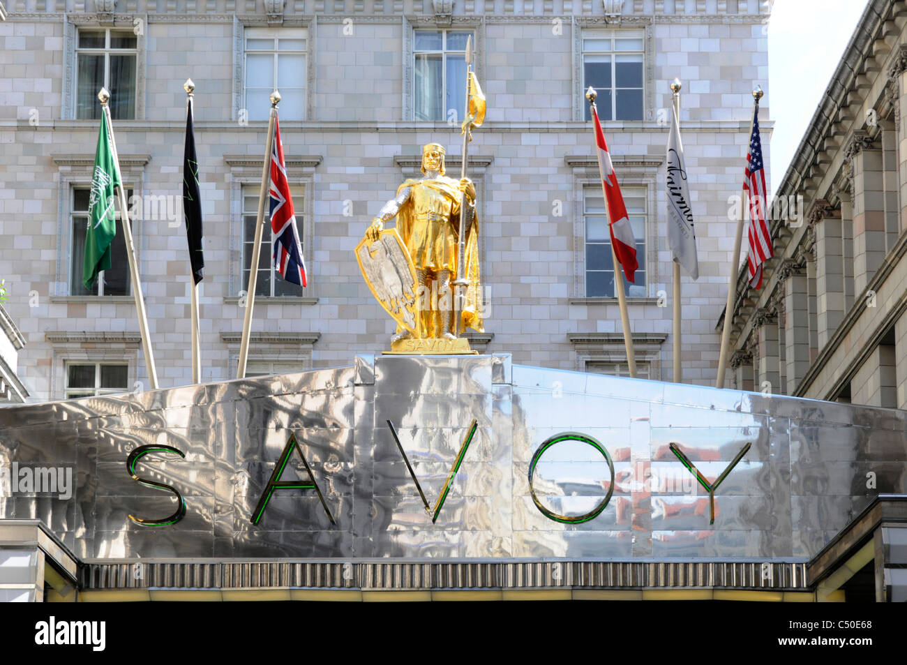 Savoy Hotel sign flags & statue above Savoy Court entrance to this London West End luxury hotel England UK - Stock Image