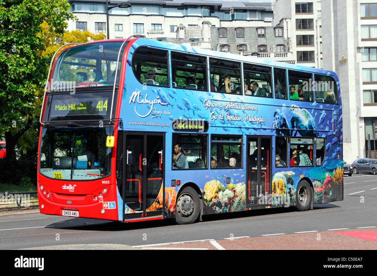 Advertising on side of London double decker bus promoting Malaysia tourism with colourful advertisement graphic - Stock Image
