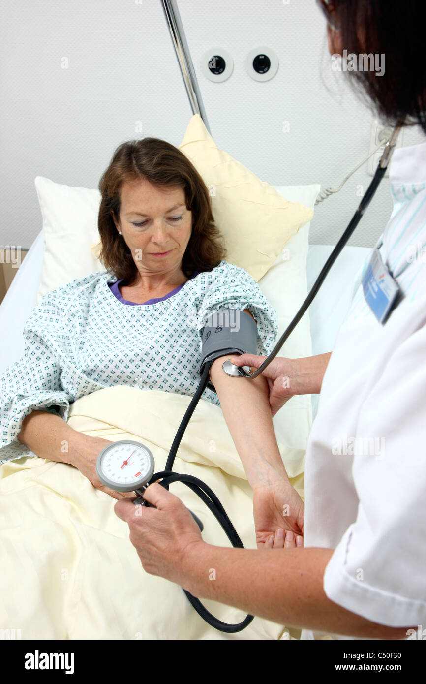 Hospital. Nurse is checking blood pressure of a female patient. - Stock Image