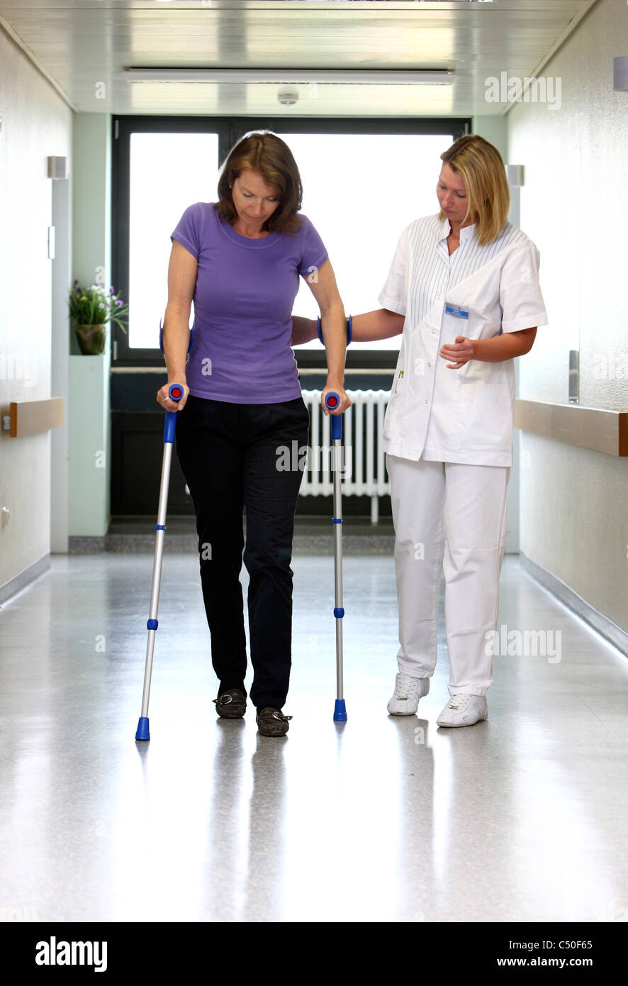 Hospital.Patient is making first steps after surgery, helped by a nurse. - Stock Image