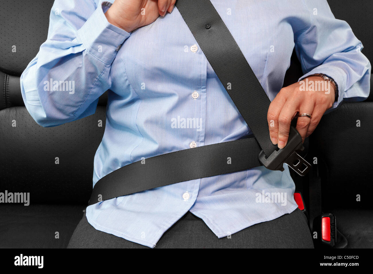 Photo of a business woman sitting in a car putting on her seat belt - Stock Image