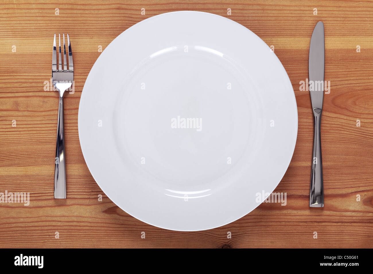 Photo of an empty white plate with knife and fork on a rustic wooden table. - Stock Image