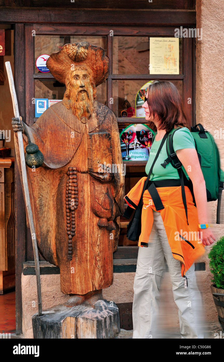 France,  St. James Way: Pilgrim passing a statue of St. James in the center of Conques - Stock Image