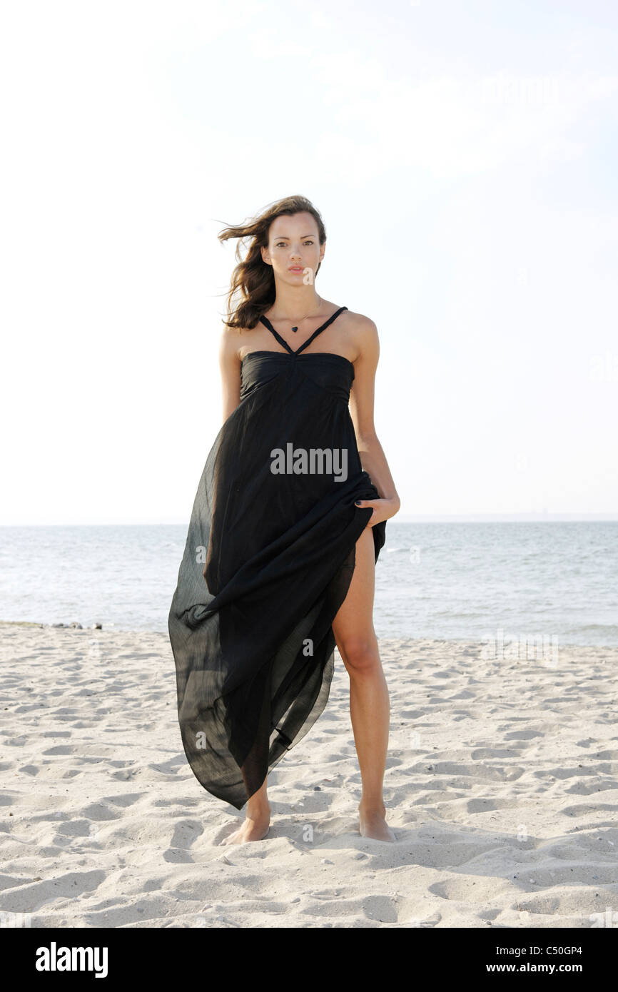 Young woman, 20+, standing in a long dress on the beach, lifestyle, sensuality, space, lightness - Stock Image