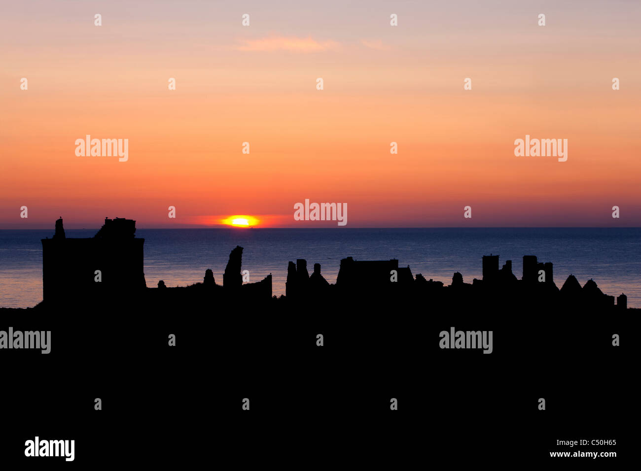 Sunrise with the silhouettes of Dunnottar Castle, near Stonehaven, Aberdeenshire, Scotland - Stock Image