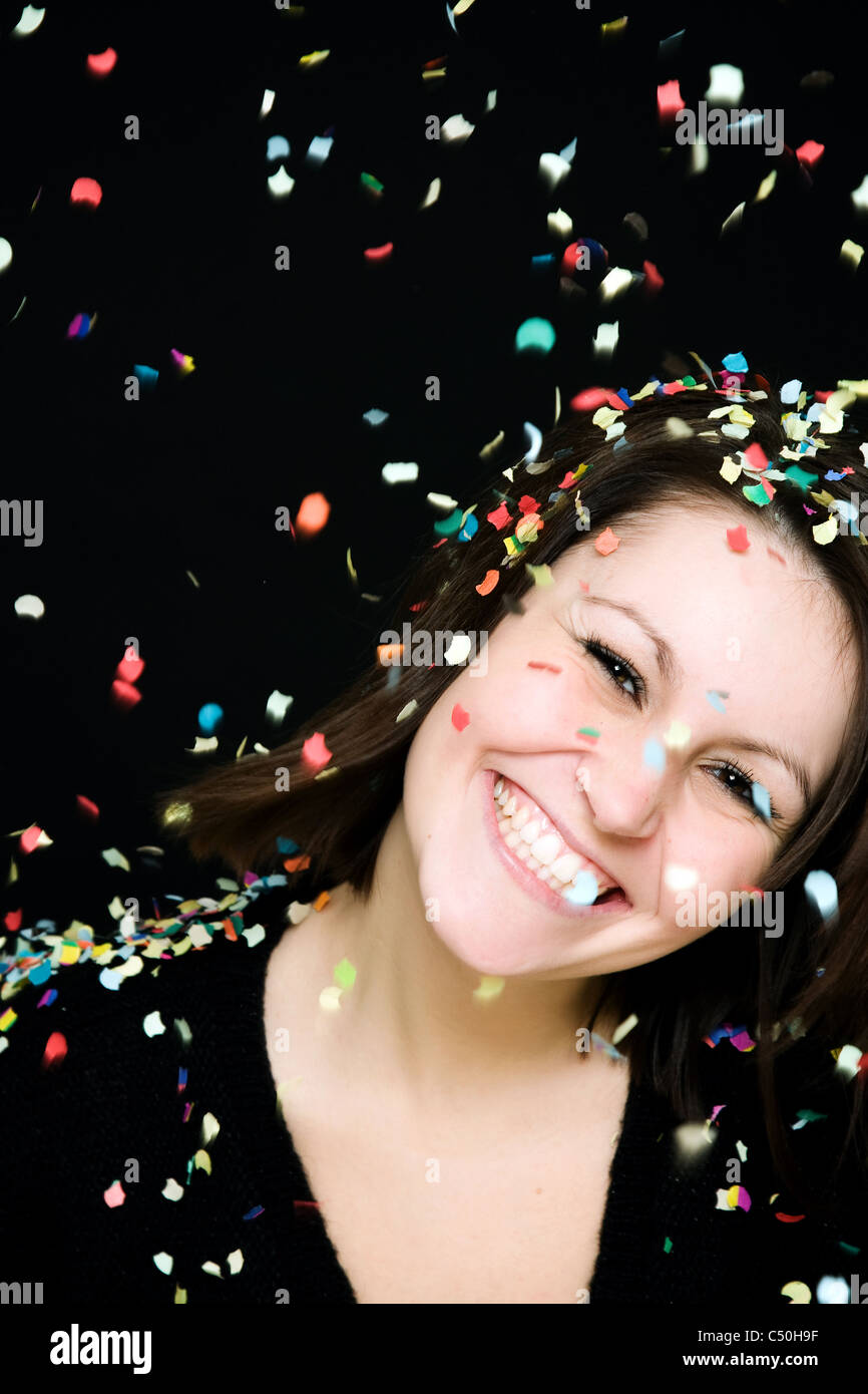 A woman laughing cheerfully in a rain of confetti - Stock Image