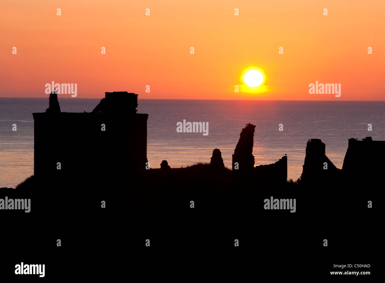 Sunrise over Dunnottar Castle and the north sea, Stonehaven, on the north east coast of Scotland - Stock Image