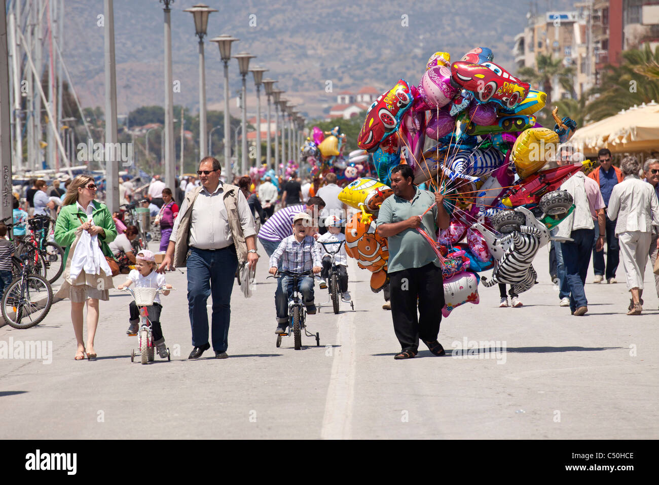 balloon vendor and kids on bicycles on the harbour promenade of the coastal port city Volos, Thessaly, Greece - Stock Image