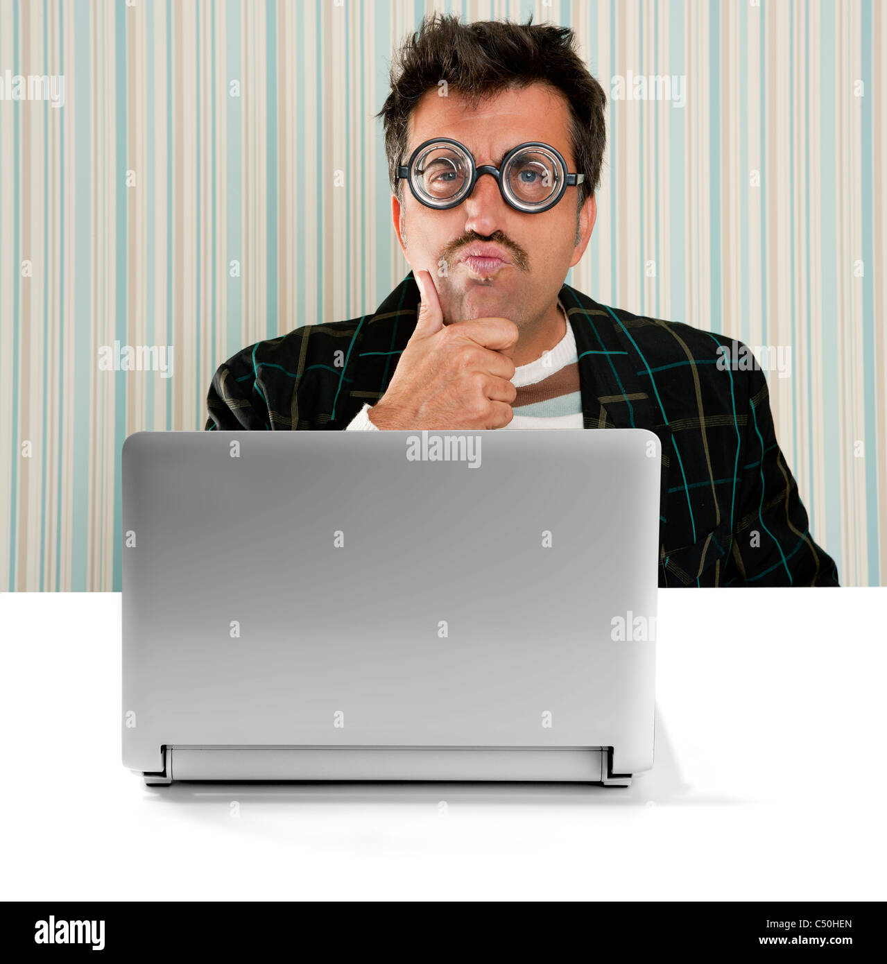 Nerd pensive man glasses silly expression laptop computer thinking a solution Stock Photo