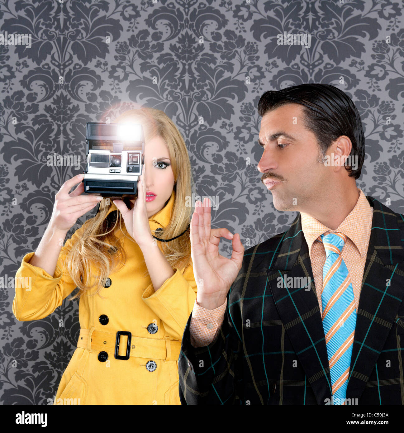geek tacky mustache man reporter fashion girl photo shoot retro wallpaper - Stock Image