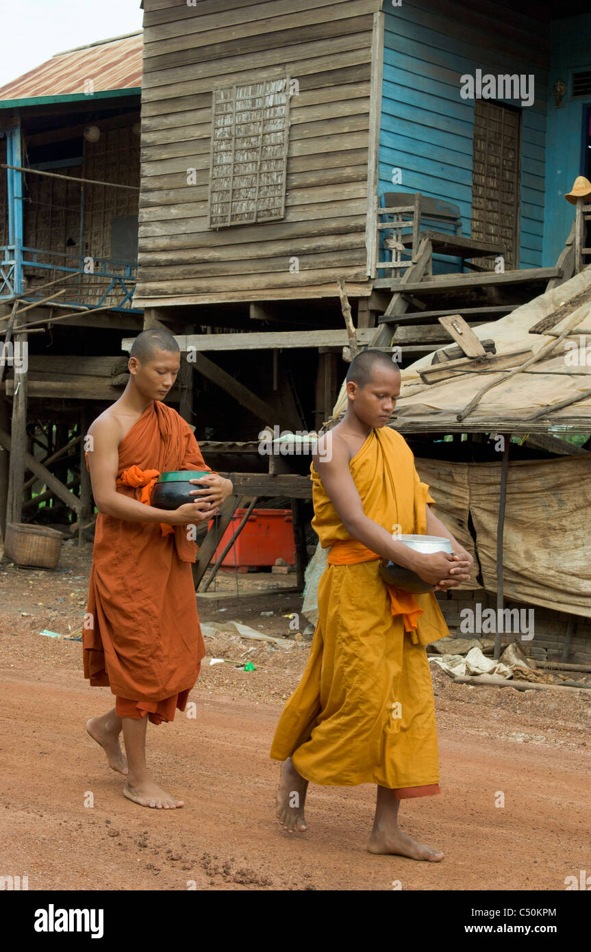 Buddhist monks on their morning alms round, Kompong Klang, on the shore of Tonle Sap lake, near Siem Reap, Cambodia Stock Photo