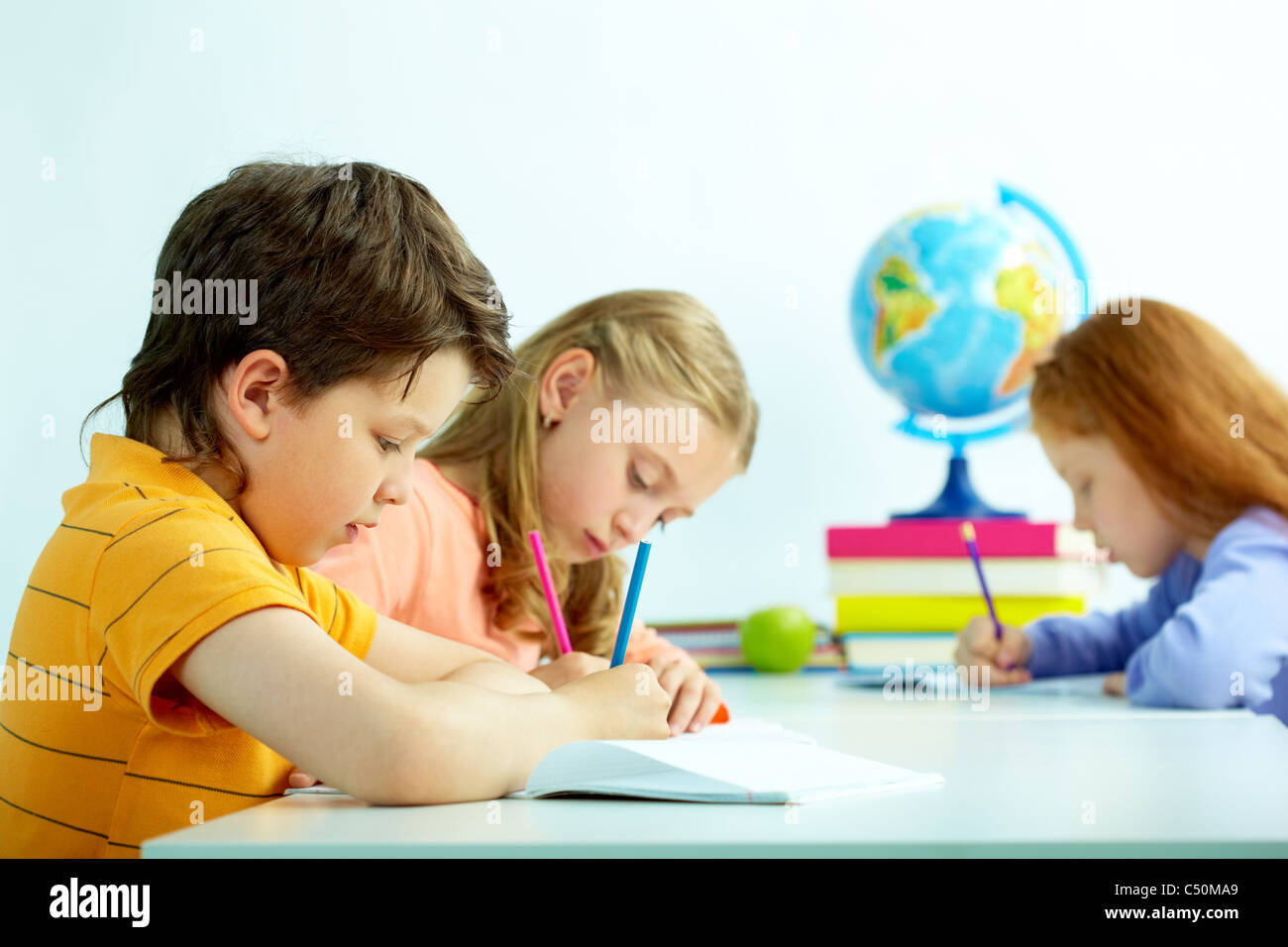 Group of schoolmates drawing at lesson - Stock Image