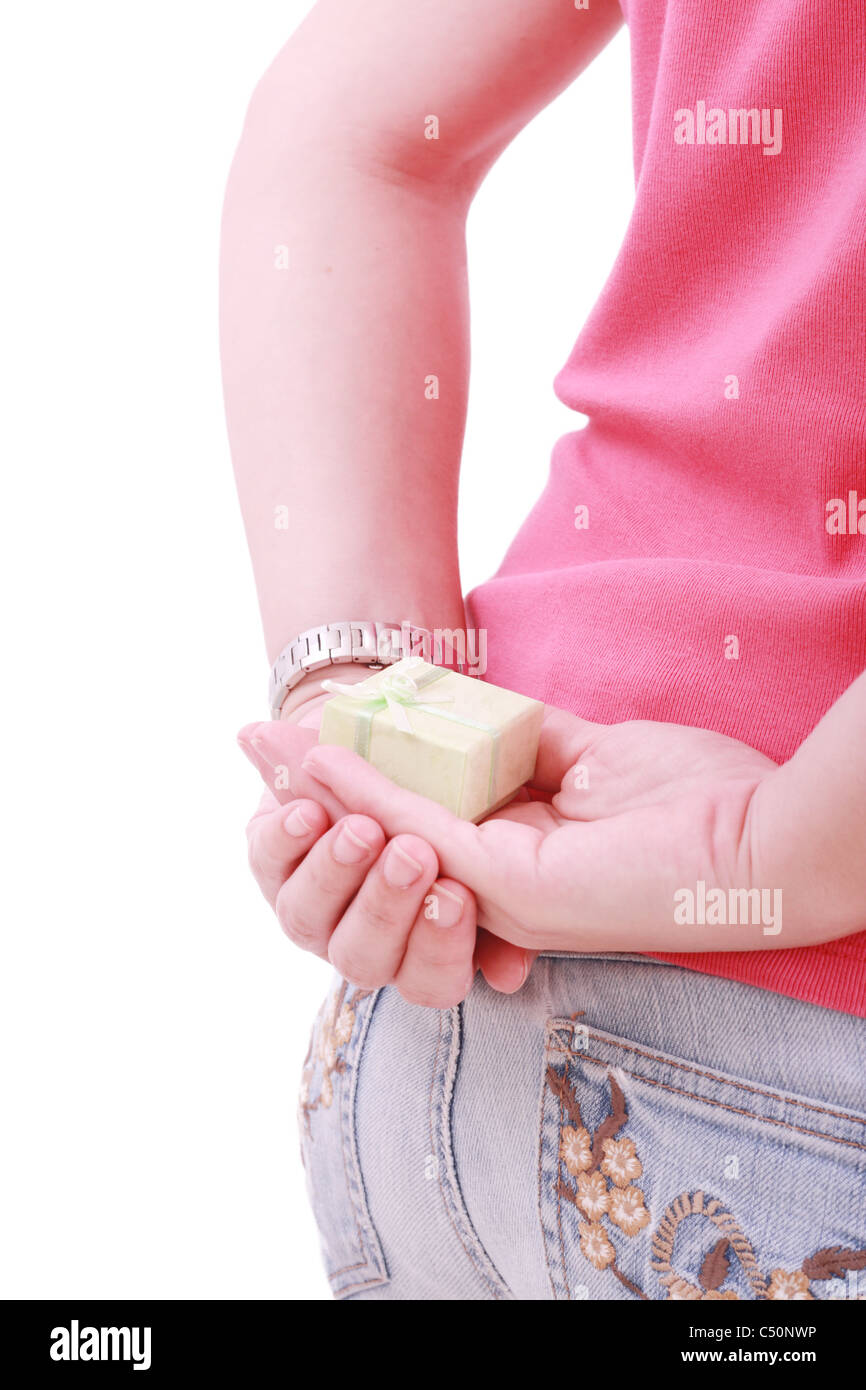 Young woman with a gift behind her back isolated - Stock Image