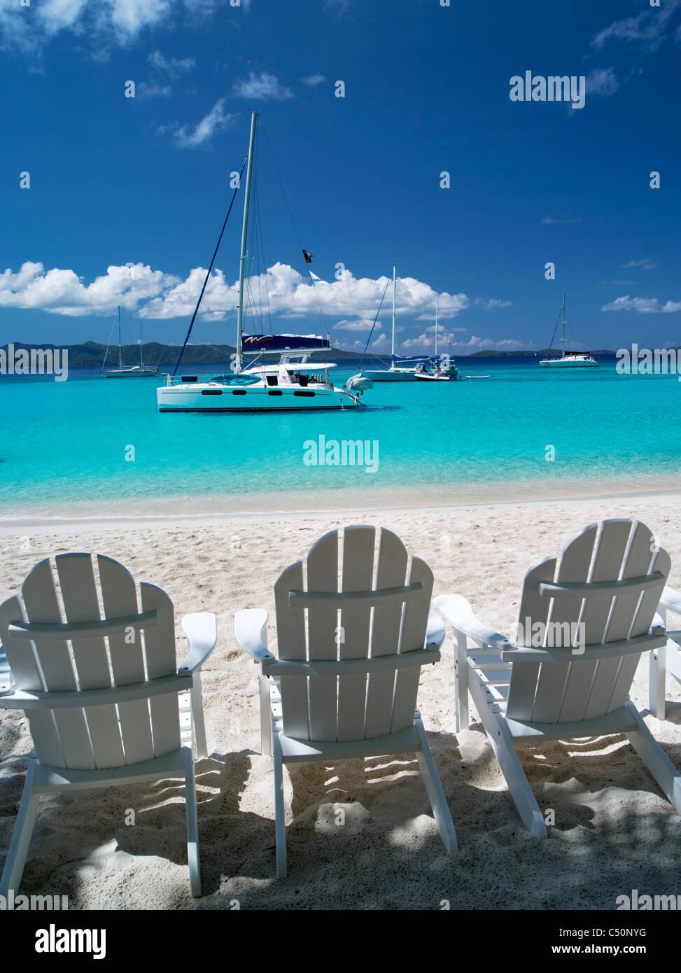 Adirondack chair boats and beach. Jost Van Dyke. British Virgin Islands - Stock Image