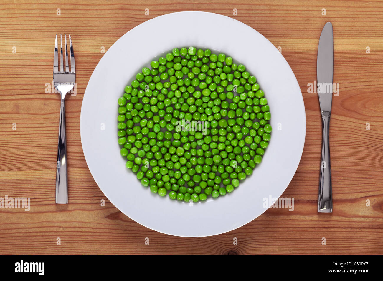 Photo of green peas on a white plate with knife and fork on a rustic wooden table. - Stock Image
