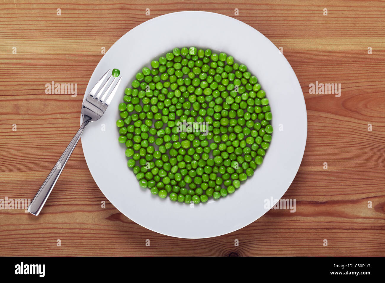 Photo of green peas on a white plate with a fork on a rustic wooden table. - Stock Image