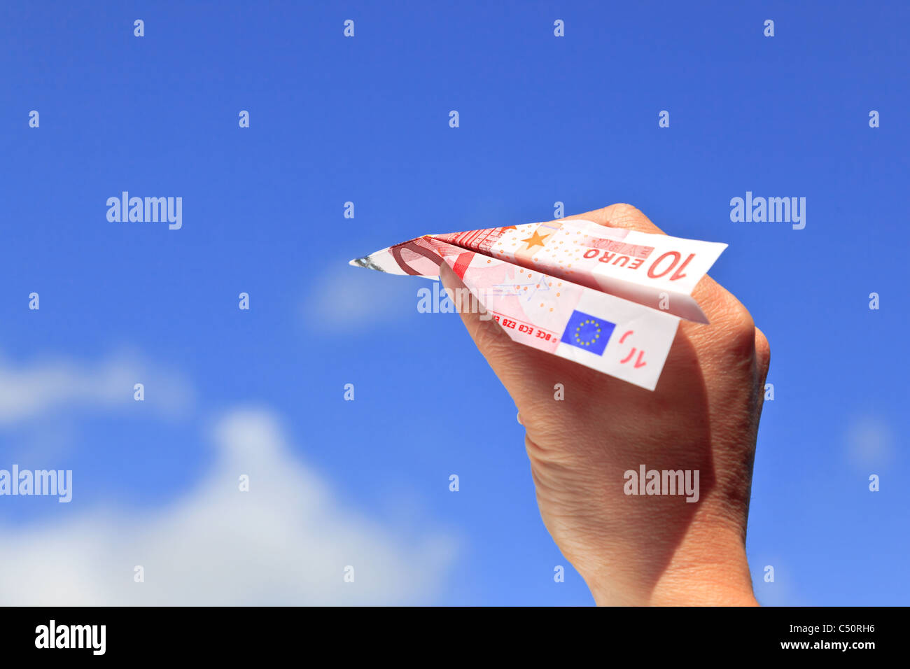 Photo of a womans hand about the launch a ten Euro banknote paper airplane into the sky on a sunny day. - Stock Image