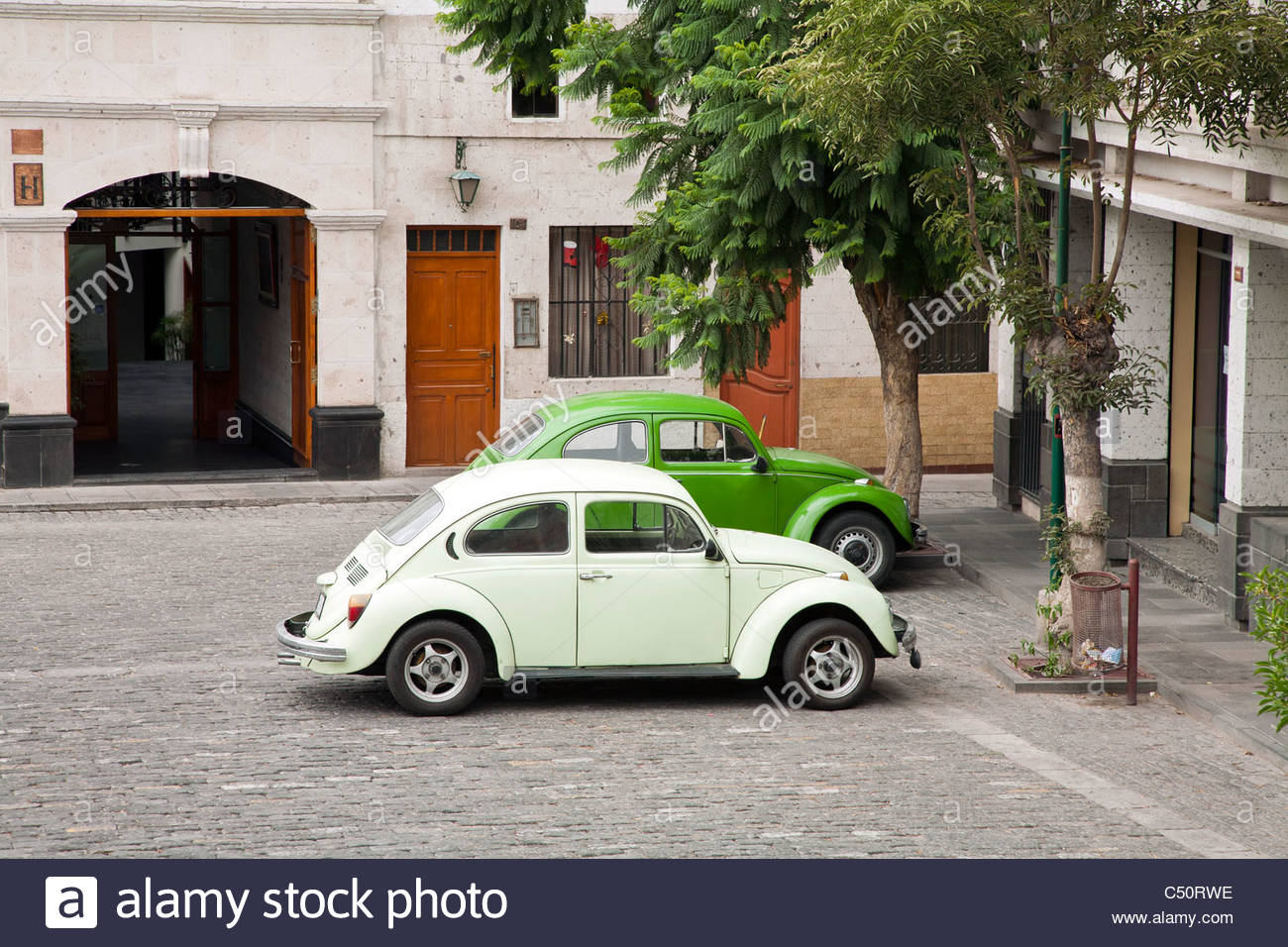 Two green Volkswagen Beetles parked side-by-side in Arequipa, Peru. Stock Photo