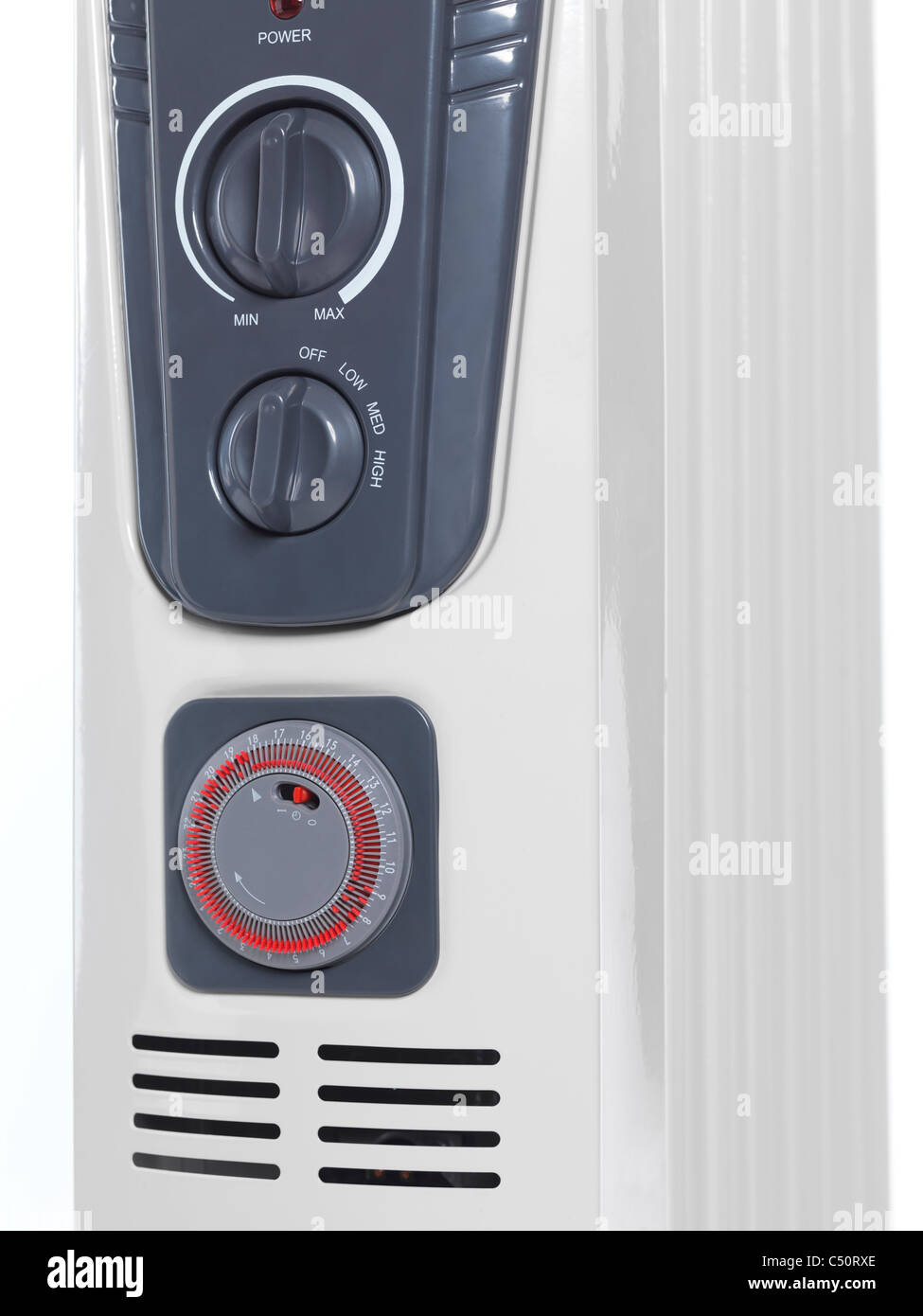 Front panel of an oil filled air heater radiator with thermostat and a timer knobs. - Stock Image