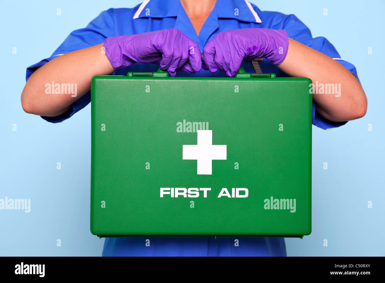 Photo of a nurse in uniform holding a green first aid kit. - Stock Image