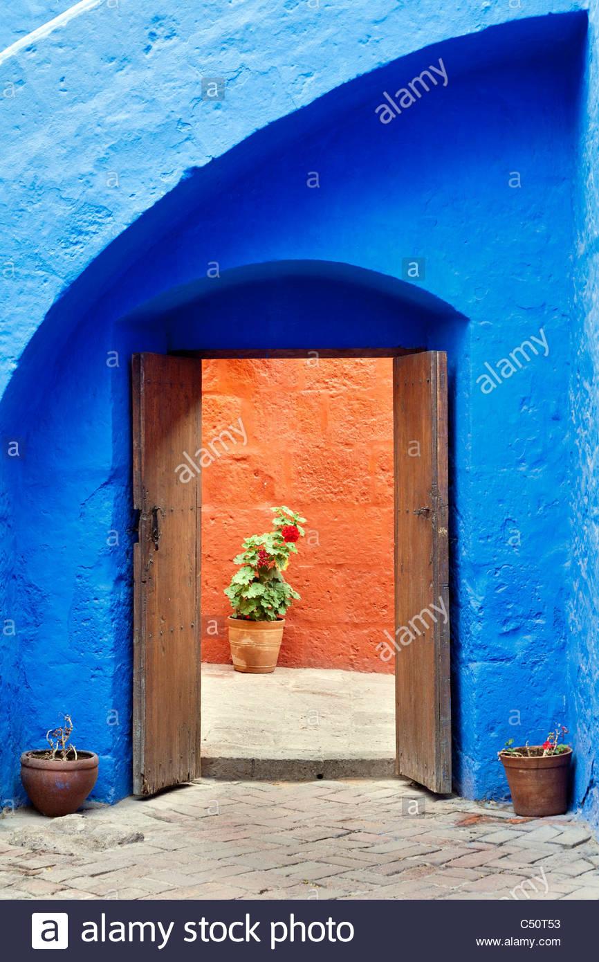 A doorway through a brightly painted blue wall at Santa Catalina Monastery, Arequipa, Peru. - Stock Image