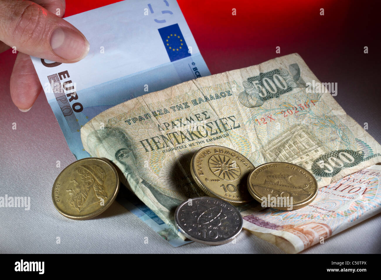 A hand pulling a euro note out from under a pile of Greek drachmas: out with the new, in with the old. - Stock Image